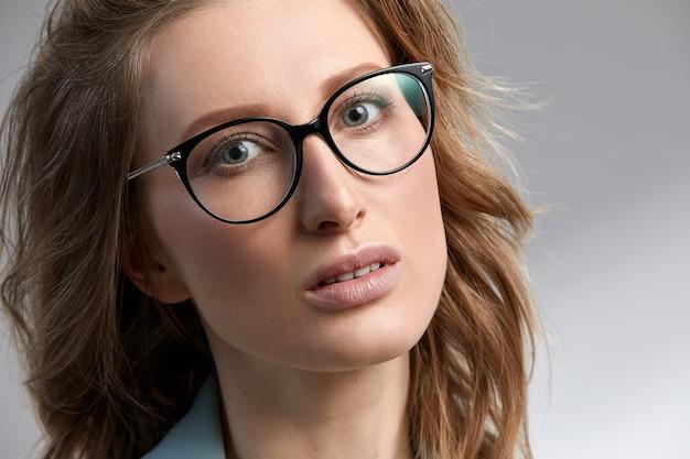 Przekonana, młody biznes kobieta 35-45 lat, blondynka w stylowe ubrania formalne i okulary, szare tło, zbliżenie. koncepcja sukcesu firmy i kariery.
