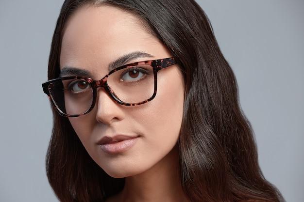 Przekonana, młody biznes kobieta 35-45 lat, brunetka w stylowe ubrania formalne i okulary, szare tło, zbliżenie. koncepcja sukcesu firmy i kariery.