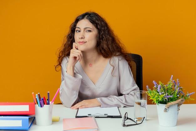 Przekonana, młody pracownik biurowy całkiem żeński siedzi przy biurku z narzędzi biurowych, kładąc rękę na brodzie na białym tle na pomarańczowym tle