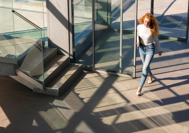 Przekonana, piękna kobieta spaceru w budynku