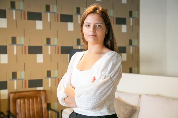 Przekonana, piękna młoda biznesowa kobieta stojąca z założonymi rękoma i pozowanie we wnętrzu coworking lub kawiarnia, patrząc na kamery