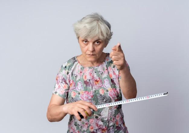 Przekonana, starsza kobieta trzyma centymetr i punkty na białym tle na białej ścianie