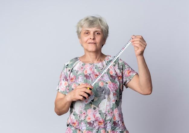 Przekonana, starsza kobieta trzyma centymetr na białym tle na białej ścianie