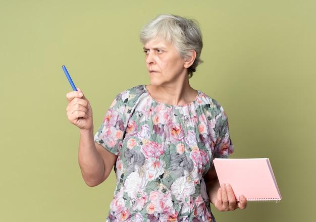 Przekonana, starsza kobieta trzyma notatnik i długopis, patrząc na bok na białym tle na oliwkowej ścianie