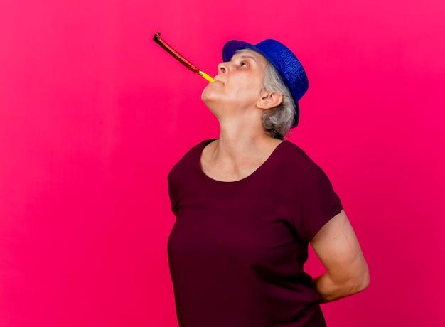 Przekonana, starsza kobieta ubrana w imprezowy kapelusz dmuchanie gwizdkiem patrząc na różowo