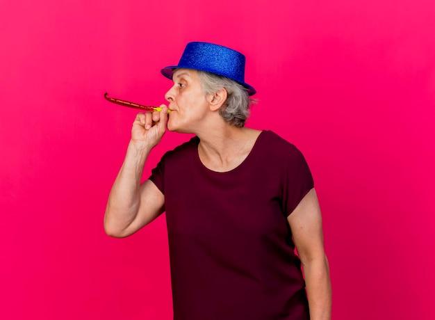 Przekonana, starsza kobieta ubrana w imprezowy kapelusz dmuchanie gwizdkiem, patrząc z boku na różowo