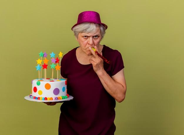 Przekonana, starsza kobieta ubrana w kapelusz imprezowy dmuchanie gwizdek, trzymając tort urodzinowy na białym tle na oliwkowej ścianie z miejsca na kopię