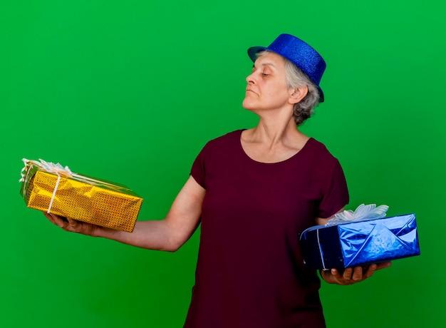 Przekonana, starsza kobieta ubrana w kapelusz partii trzyma i patrzy na pudełka na prezenty na zielono