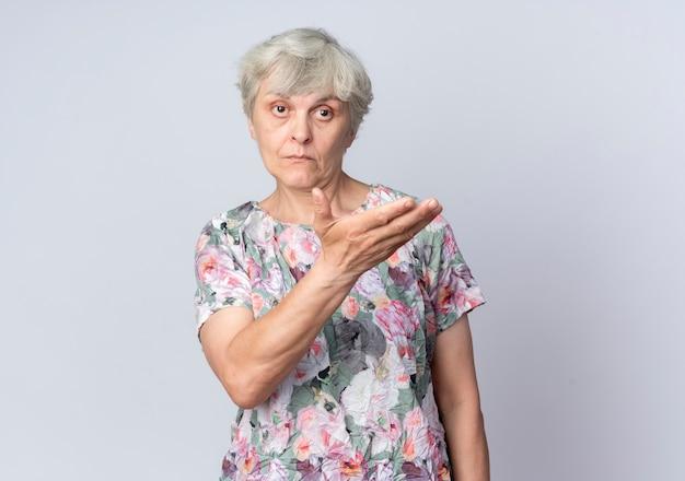 Przekonana, starsza kobieta wskazuje na bok ręką na białym tle na białej ścianie