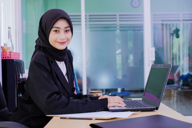 Przekonana, szczęśliwy młody biznes kobieta siedzi na biurko, pracując na komputerze