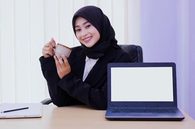 Przekonana, szczęśliwy młody biznes kobieta siedzi przy biurku, trzymając filiżankę kawy