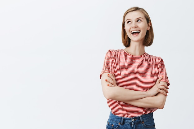 Przekonana, uśmiechnięta młoda kobieta krzyżuje ramiona w klatce piersiowej i patrząc szczęśliwy w lewym górnym rogu