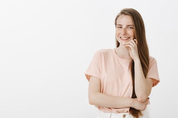 Przekonana, uśmiechnięta nastoletnia dziewczyna pozuje na białej ścianie