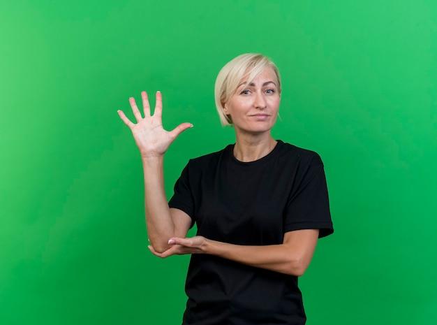 Przekonana w średnim wieku blond słowiańska kobieta kładzie rękę na łokciu pokazując pięć ręką odizolowaną na zielonej ścianie z miejsca na kopię