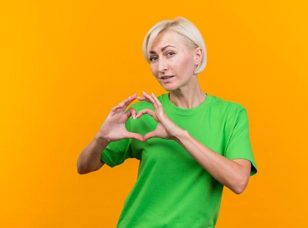Przekonana w średnim wieku blond słowiańska kobieta, patrząc na przód robi znak serca na białym tle na żółtej ścianie z miejsca na kopię