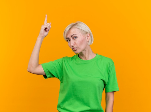 Przekonana w średnim wieku blond słowiańska kobieta patrząc na przód skierowaną w górę na białym tle na żółtej ścianie z miejsca na kopię