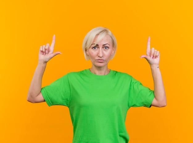 Przekonana w średnim wieku blond słowiańska kobieta patrząc na przód skierowaną w górę na białym tle na żółtej ścianie