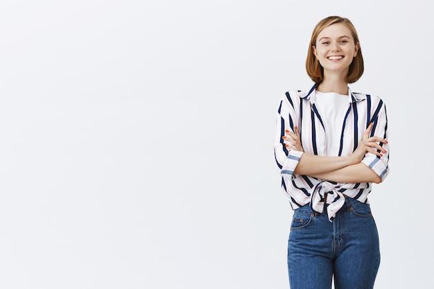 Przekonana, że kobieta młody zawodowy krzyż ramiona w klatce piersiowej i patrząc zadowolony, uśmiechnięty