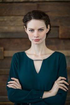 Przekonana, żeński biznes wykonawczy stojący z rękami skrzyżowanymi w biurze