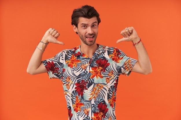 Przekonany, atrakcyjny młody człowiek z zarostem w hawajskiej koszuli, stojąc i wskazując na siebie kciukami na obu dłoniach