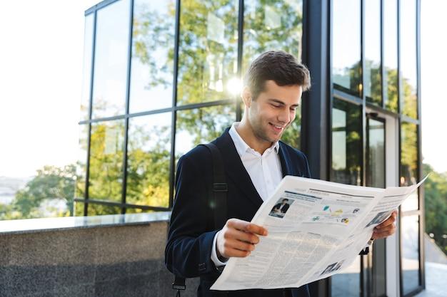 Przekonany, biznesmen czytanie gazety stojąc na zewnątrz
