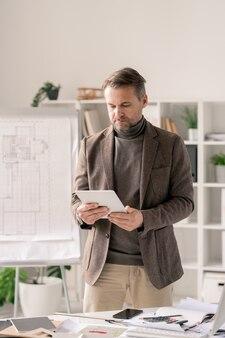 Przekonany, dojrzały architekt w wizytowym przewijaniu w tablecie stojąc przy biurku na tle tablicy