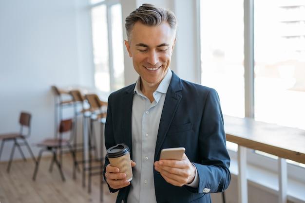 Przekonany, dojrzały mężczyzna, trzymając smartfon i filiżankę kawy, czytając wiadomości, komunikację online w biurze