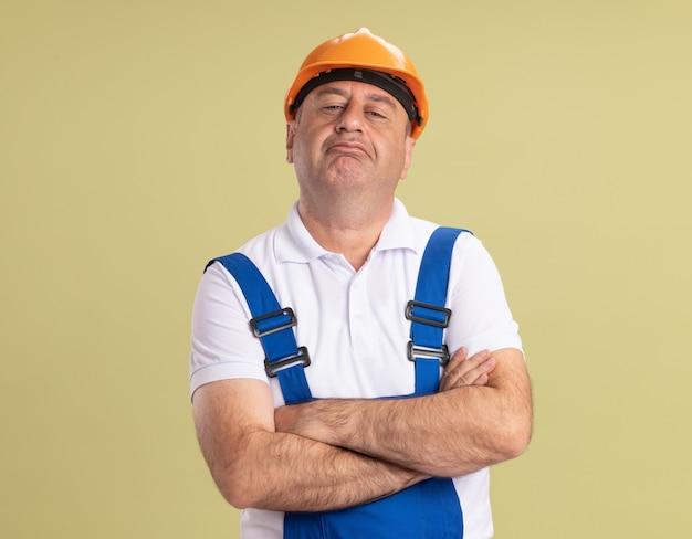 Przekonany, dorosły budowniczy mężczyzna stoi ze skrzyżowanymi rękami na oliwkowej zieleni