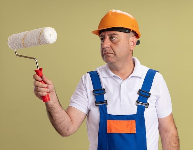 Przekonany, dorosły budowniczy mężczyzna trzyma i patrzy na szczotkę rolkową na białym tle na oliwkowozielonej ścianie