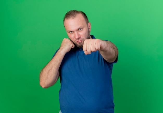 Przekonany, dorosły człowiek słowiański robi gest bokserski na białym tle na zielonej ścianie z miejsca na kopię