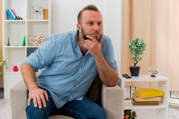 Przekonany, dorosły mężczyzna słowiański siedzi na fotelu, kładąc dłoń na brodzie, patrząc z boku w salonie