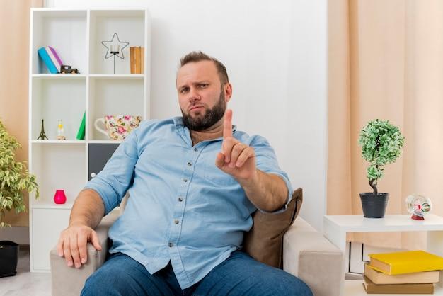 Przekonany, dorosły mężczyzna słowiański siedzi na fotelu, pokazując palec wskazujący, patrząc do wnętrza zaprojektowanego salonu