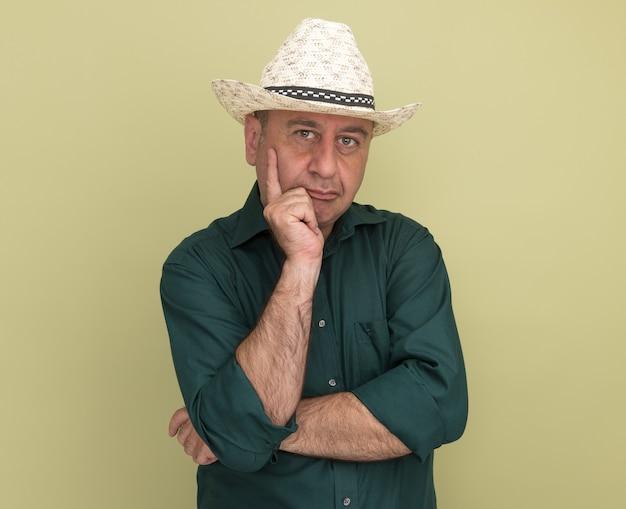 Przekonany, mężczyzna w średnim wieku, ubrany w zielony t-shirt i kapelusz, kładąc rękę na policzku na białym tle na oliwkowej ścianie
