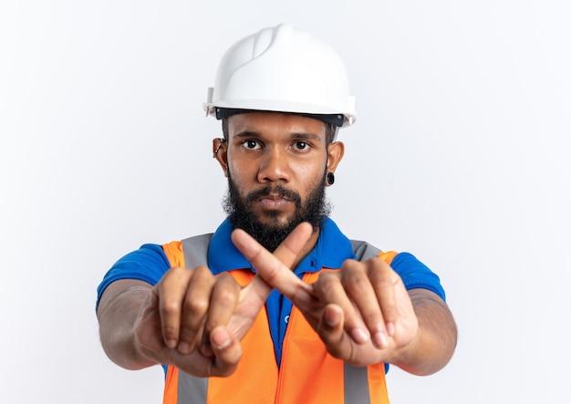 Przekonany, młody afro-amerykański budowniczy mężczyzna w mundurze z hełmem bezpieczeństwa skrzyżowanymi palcami, gestem bez znaku na białym tle na białym tle z miejsca kopiowania