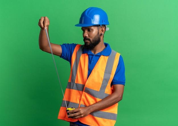Przekonany, młody afro-amerykański budowniczy mężczyzna w mundurze z hełmem ochronnym, trzymając i patrząc na taśmę mierniczą na białym tle na zielonym tle z kopią przestrzeni