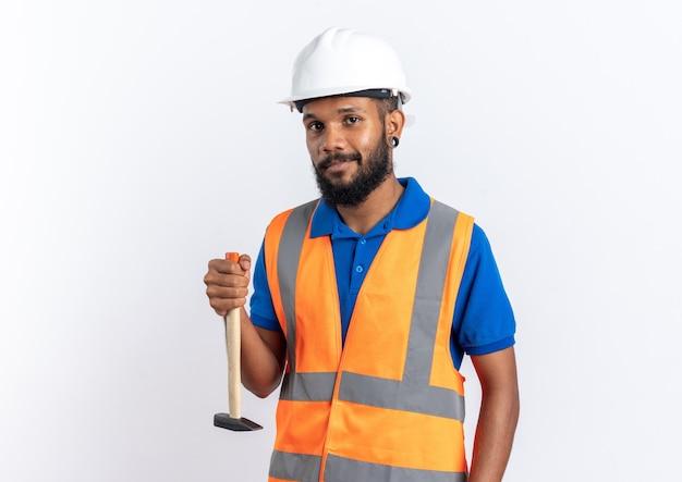 Przekonany, młody afro-amerykański budowniczy mężczyzna w mundurze z hełmem ochronnym trzymając młot do góry nogami na białym tle na białej ścianie z kopią przestrzeni