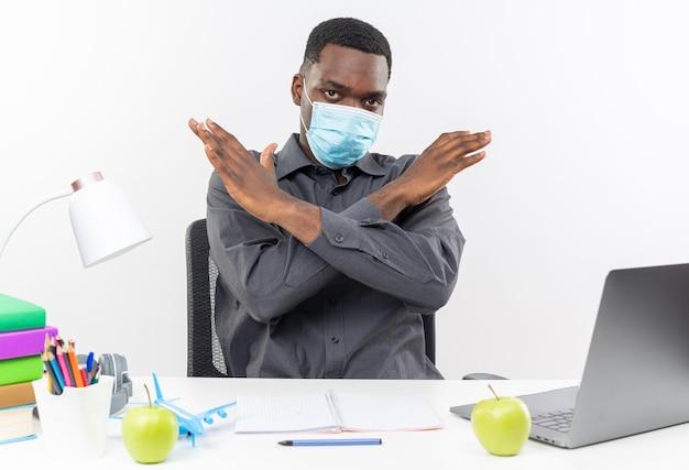 Przekonany, młody afroamerykański uczeń noszący maskę medyczną siedzący przy biurku ze szkolnymi narzędziami krzyżującymi ręce, gestykulujący bez znaku