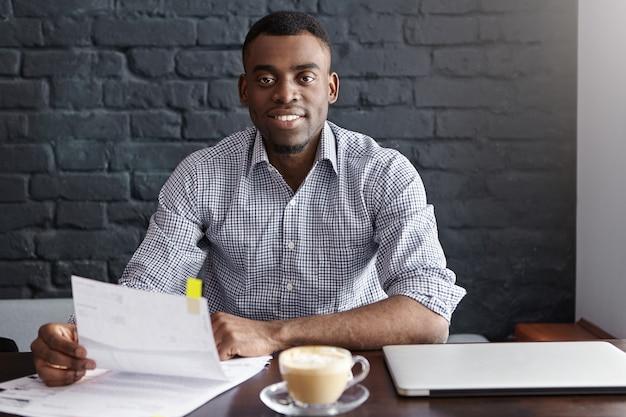 Przekonany, młody biznesmen afryki na sobie formalną koszulę siedzi przy stole z laptopem, kubkiem i papierami