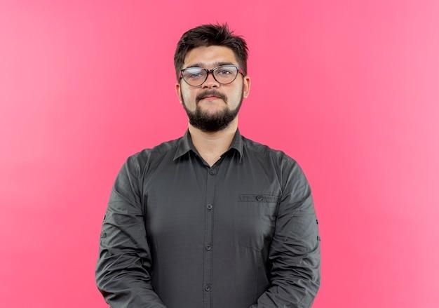 Przekonany, młody biznesmen w okularach na różowym tle