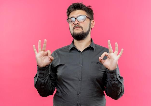 Przekonany, młody biznesmen w okularach, pokazując okey gest na białym tle na różowej ścianie