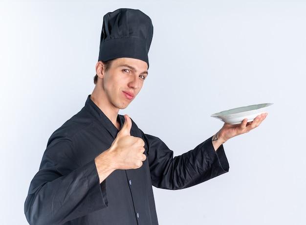 Przekonany, młody blond mężczyzna kucharz w mundurze szefa kuchni i czapce stojącej w widoku profilu rozciągający się talerz patrząc na kamerę pokazujący kciuk na białym tle na białej ścianie