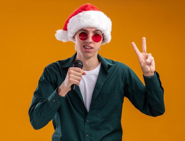 Przekonany, młody blondyn w kapeluszu santa i okularach mówi do mikrofonu patrząc na kamery robi znak pokoju na białym tle na pomarańczowym tle