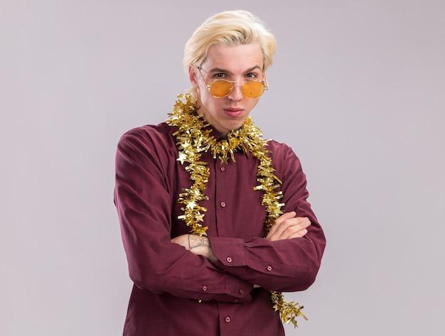 Przekonany, młody blondyn w okularach z blichtrową girlandą wokół szyi stojący z zamkniętą postawą, patrząc na kamerę na białym tle na białym tle z miejsca kopiowania