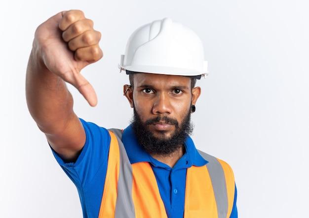 Przekonany, młody człowiek afro-amerykański budowniczy w mundurze z hełmem bezpieczeństwa kciukiem w dół na białym tle na białym tle z miejsca kopii