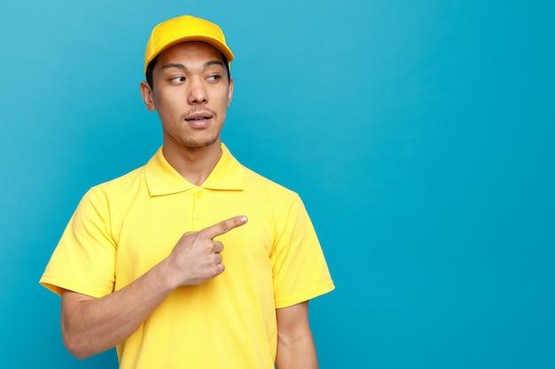 Przekonany, młody człowiek dostawy ubrany w mundur i czapkę, patrząc i wskazując na bok