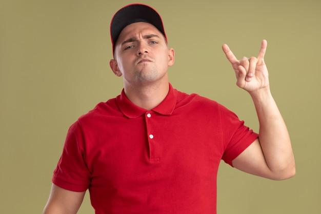 Przekonany, młody człowiek dostawy ubrany w mundur i czapkę pokazując gest kozy na białym tle na oliwkowej ścianie