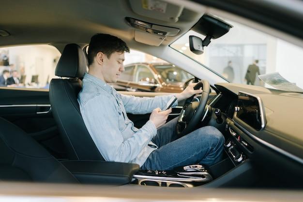 Przekonany, młody człowiek korzystający z telefonu komórkowego siedzi za kierownicą samochodu