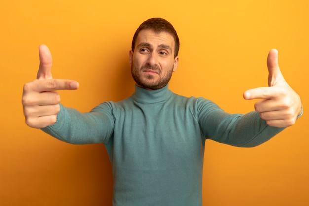 Przekonany, młody człowiek, patrząc na bok, wskazując na przestrzeń przed nim na białym tle na pomarańczowej ścianie