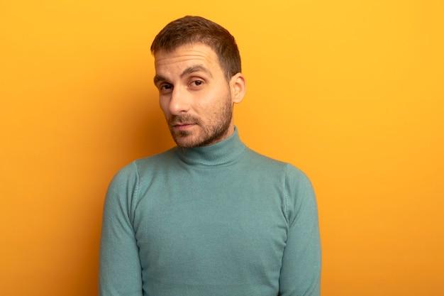 Przekonany, młody człowiek, patrząc z przodu na białym tle na pomarańczowej ścianie