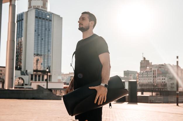 Przekonany, młody człowiek posiadający walcowane matę do jogi i patrząc na piękny widok rano na duże miasto. koncepcja działań rano. jasne słońce na tle. czarna odzież sportowa.
